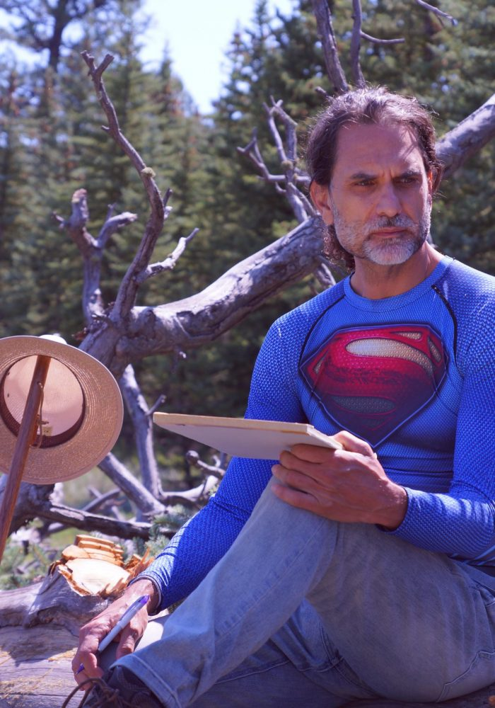 A photo of Jim in a Superman shirt, sitting on a collection of branches. Jim is holding a notepad and looking into the distance.